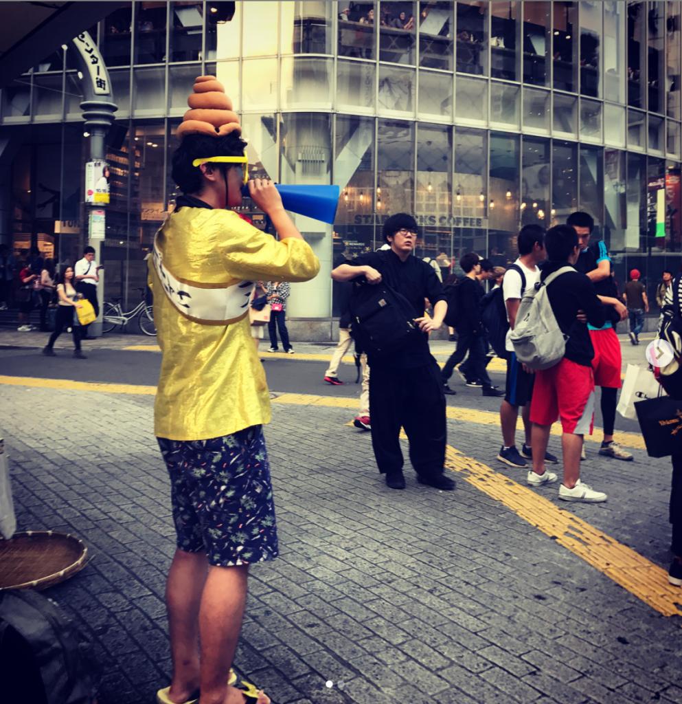 guy broadcasting on microphone wearing poop emoji hat